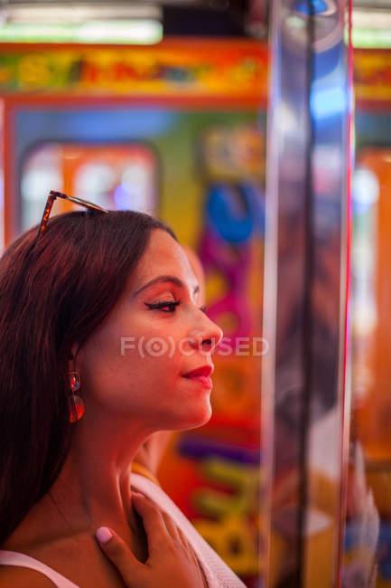 Приваблива жінка, яка дивиться на карнавал червоним світлом. — стокове фото