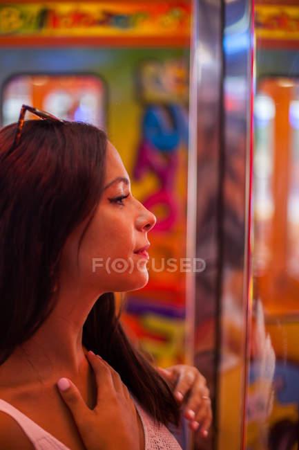 Seitenansicht der attraktiven, entzückten Frau, die im Rotlicht auf den Stand am Karneval starrt — Stockfoto