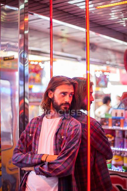 Усмішка зміст випадковий чоловік стояв біля дзеркальної стіни на карнавалі з різнокольоровими неоновими вогнями — стокове фото