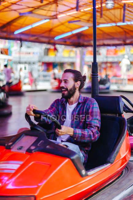 Joyeux homme souriant en vêtements décontractés s'amuser et conduire voiture d'attraction colorée à la foire — Photo de stock