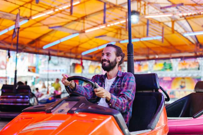 Homem sorridente alegre em roupas casuais se divertindo e dirigindo carro atração colorida no recinto de feiras — Fotografia de Stock