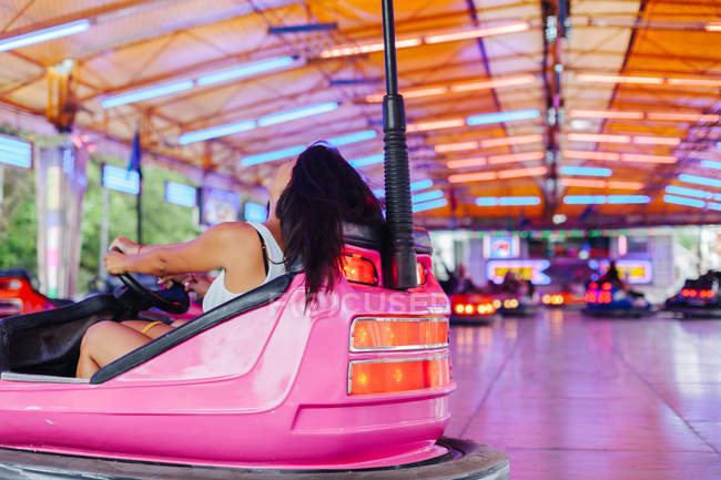 Cheerful woman in casual outfit having fun and driving attraction car at carnival — Stock Photo