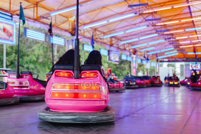 Mulheres alegres em roupas casuais se divertindo e dirigindo carro atração colorida no carnaval — Fotografia de Stock