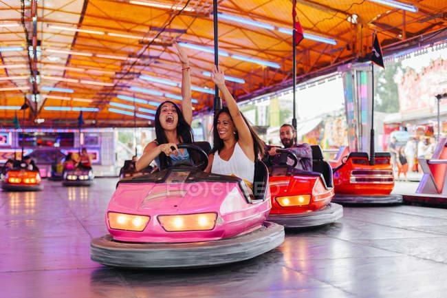 Веселые женщины в повседневной одежде веселятся и водят красочный аттракцион автомобиль на карнавале — стоковое фото