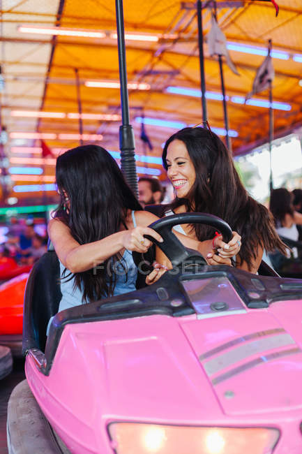 Cheerful women in casual outfit having fun and driving colourful attraction car at carnival — Photo de stock