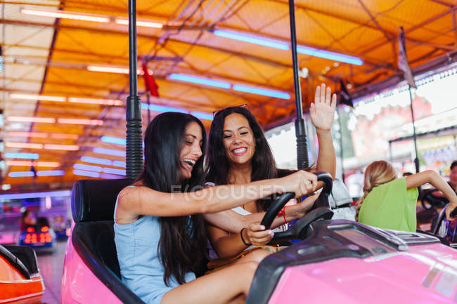 Cheerful women in casual outfit having fun and driving colourful attraction car at carnival — Stock Photo