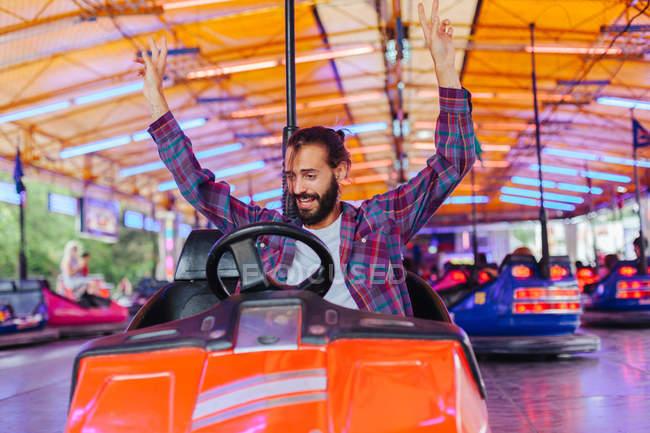 Радостный улыбающийся мужчина в повседневной одежде веселится и водит красочный аттракцион автомобиль на ярмарке — стоковое фото