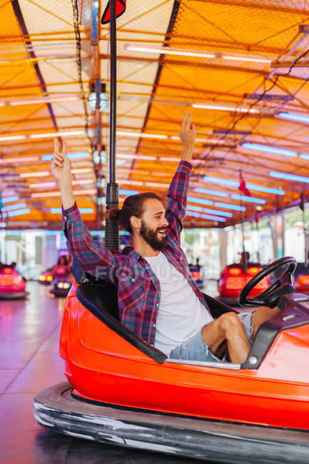 Joyful smiling man in casual clothes having fun and driving colourful attraction car at fairground — Stock Photo