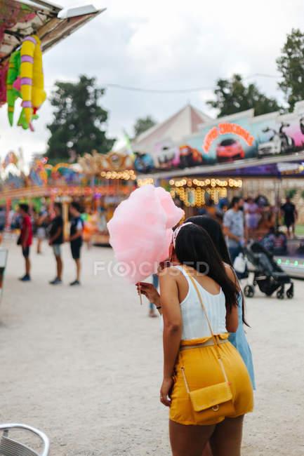 Грайливі жінки в модному одязі з бавовняними цукерками стоять поруч з привабливістю неоновими вогнями на ярмарку. — стокове фото