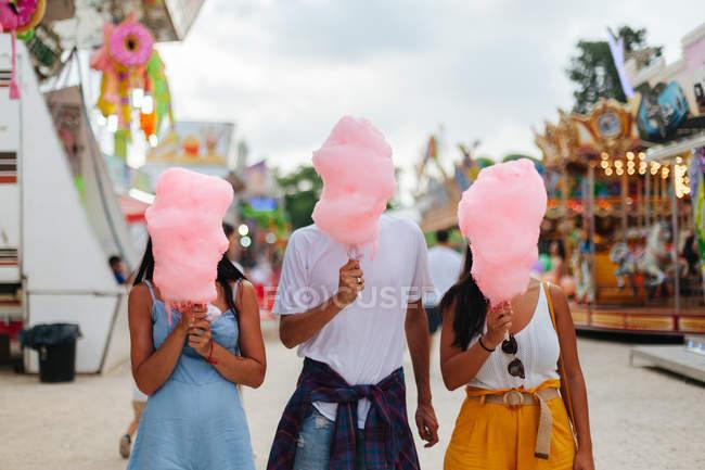 Грайливі усміхнені жінки і чоловік у модному одязі, тримаючи бавовняні цукерки, стоячи поруч з привабливістю неоновими вогнями. — стокове фото
