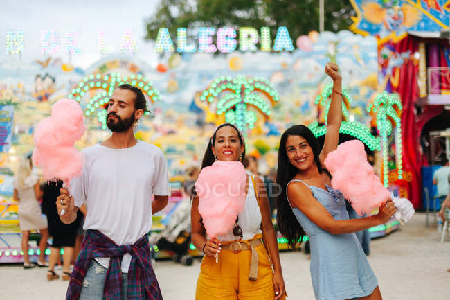 Playful smiling women and man in trendy clothes holding cotton candies while standing next to attraction with neon lights — стокове фото