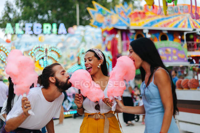 Playful smiling women and man in trendy clothes eating cotton candies while standing next to attraction with neon lights — Stock Photo