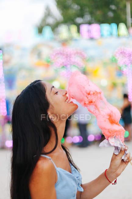 Seitenansicht einer charmanten Frau, die Zuckerwatte isst, während sie neben einer Attraktion mit Neonlicht auf einem Jahrmarkt steht — Stockfoto