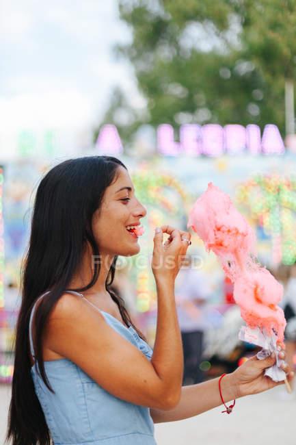 Вигляд чарівної жінки, що їсть бавовняні цукерки, стоячи поруч, з неоновими вогнями на ярмарку. — стокове фото