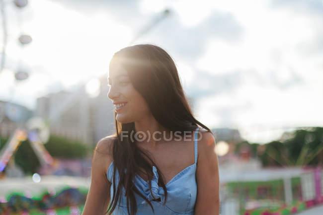 Wehmütige ruhige Frau mit langen Haaren im Anzug steht an einem windigen Sommertag neben Attraktion auf dem Festplatz — Stockfoto