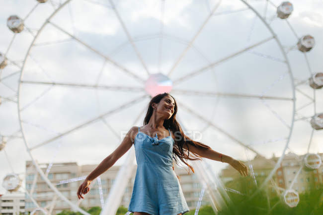 Wistful calm woman with long hair in sundress standing beside attraction at fairground on summer windy day — Stock Photo