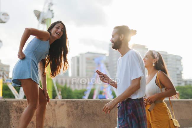 Беззаботные загорелые люди в повседневной одежде веселятся на парапете на колесе обозрения в парке развлечений летом — стоковое фото