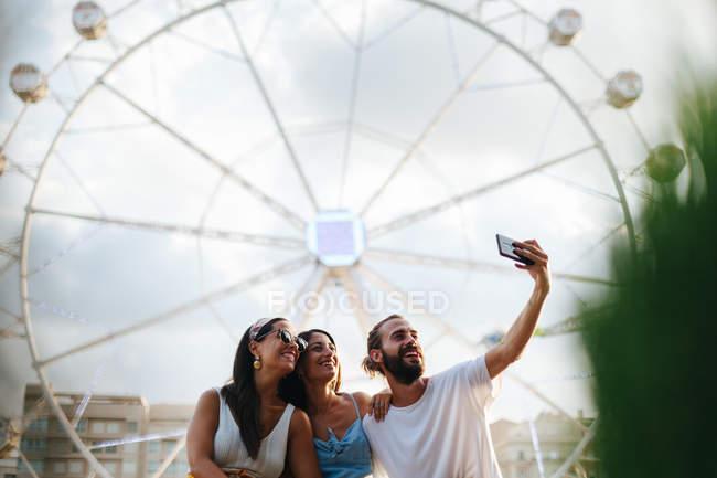 Веселі посміхаються засмаглі засмаглі люди, які роблять фото на смартфоні, стоячи поруч із притяганням до карнавалу. — стокове фото