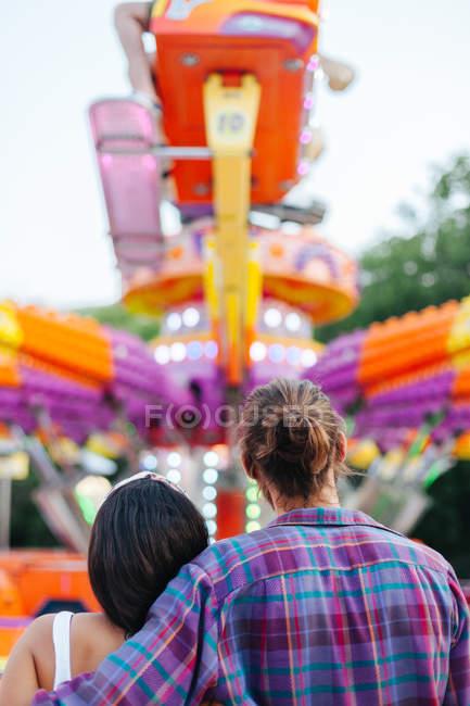 Подружня пара із захопленням спостерігає за барвистою привабливістю сонячної забави. — стокове фото