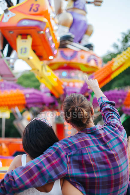 Casual couple looking up in excitement while visiting colourful attraction at sunny funfair — стокове фото