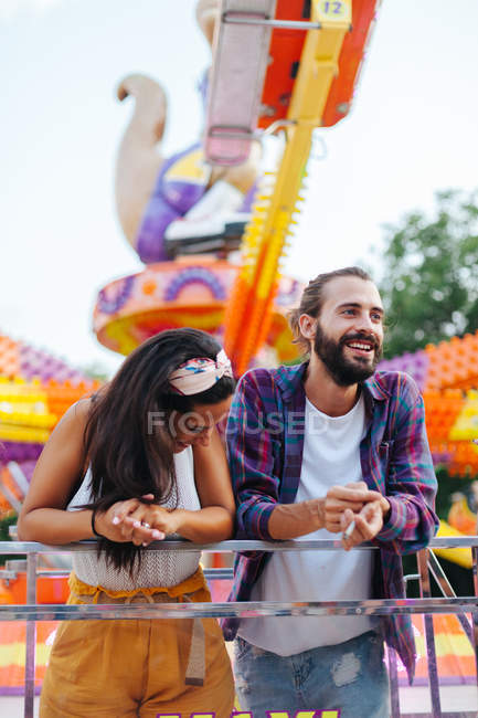 Amused casual couple looking up in excitement while visiting colourful attraction at sunny funfair — стокове фото