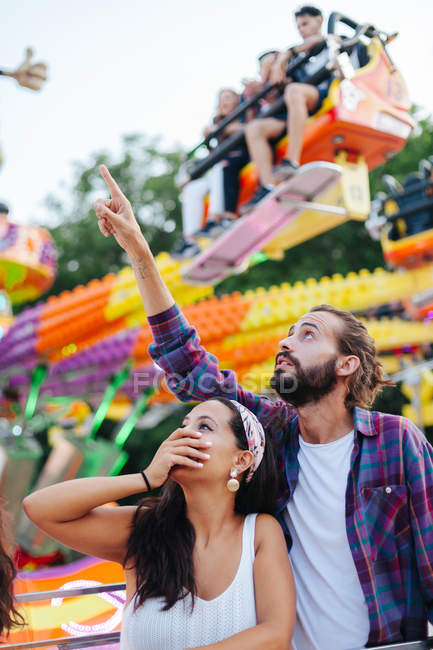 Amused casual couple looking up in excitement while visiting colourful attraction at sunny funfair — Stock Photo