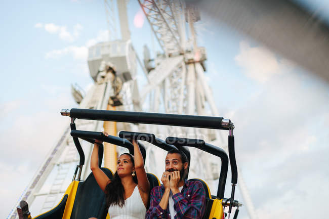 Enthusiastic carefree woman and man having fun while enjoying ride at colourful attraction at sunny funfair — Photo de stock