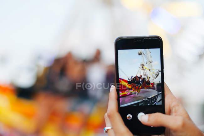 Imagem cortada de mulher tirando foto de amigos curtindo passeio na atração — Fotografia de Stock