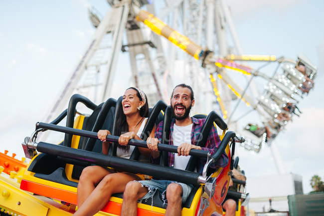 Enthusiastic carefree woman and man having fun while enjoying ride at colourful attraction at sunny funfair — стокове фото