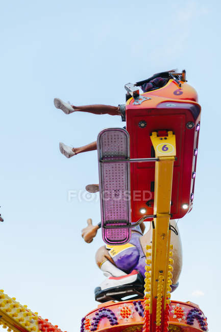 Carefree woman and man having fun while enjoying ride at colourful attraction at sunny funfair — стокове фото