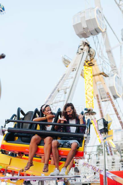 Захоплююча безтурботна жінка і чоловік, які розважаються під час їзди на квітучій принаді на сонячній ярмарці. — стокове фото
