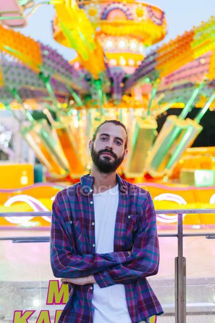 Спокійний гіпстер у звичайному одязі стоїть зі схрещеними руками біля освітленої кольорової каруселі на ярмарку. — стокове фото