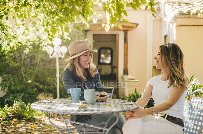 Side view of young cheerful casual girlfriends talking and drinking tea at table in garden of old house — стокове фото