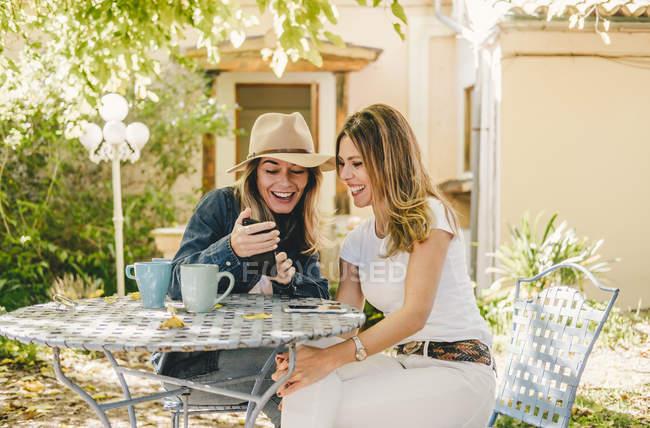 Казуальные женщины делят мобильный телефон и пьют чай, сидя за столом в зеленом саду — стоковое фото
