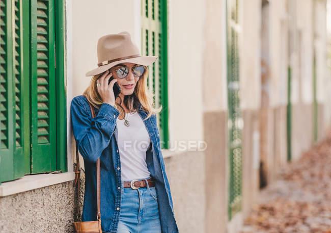 Vista lateral da jovem mulher sorridente usando telefone celular e inclinando-se no prédio de pedra fora — Fotografia de Stock