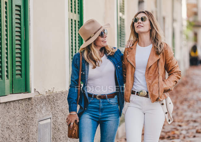 Stylish relaxed women chatting to each other happily while walking down street — стокове фото