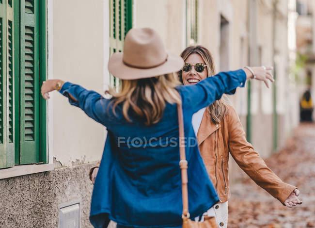 Веселые женщины встречаются и приветствуют друг друга объятиями на городской улице с листвой — стоковое фото