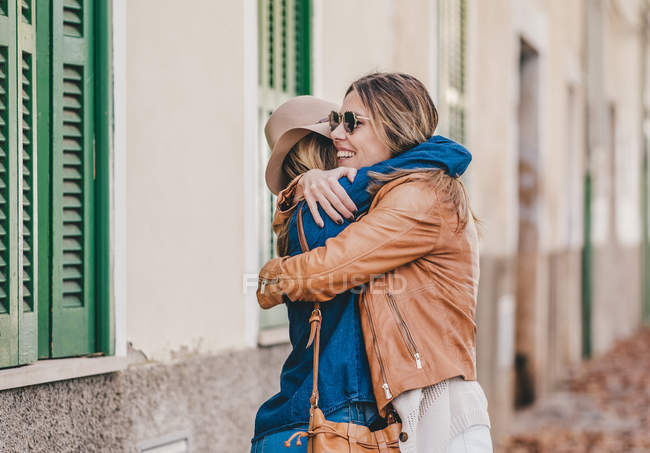 Cheerful women meeting and greeting each other with hug on town street with foliage — Stock Photo