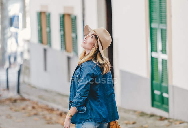 Stylish relaxed woman walking down street and looking up the building — Stock Photo