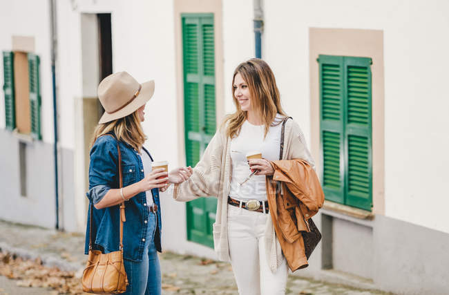 Stylish relaxed women chatting happily while walking down street having coffee in cups — стокове фото