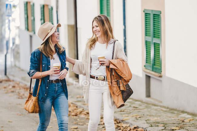 Стильные расслабленные женщины счастливо болтают, гуляя по улице, выпивая кофе в чашках. — стоковое фото