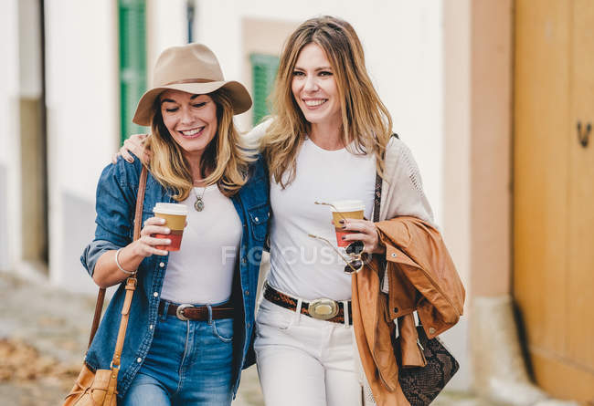 Stylish relaxed women chatting happily while walking down street having coffee in cups — Stock Photo