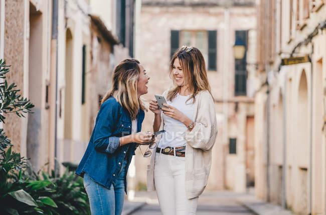 Jovens atraentes mulheres sorridentes andando e mensagens com telefones celulares na rua — Fotografia de Stock