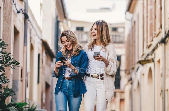 Молодые привлекательные улыбающиеся женщины ходят и общаются с мобильными телефонами на улице — стоковое фото