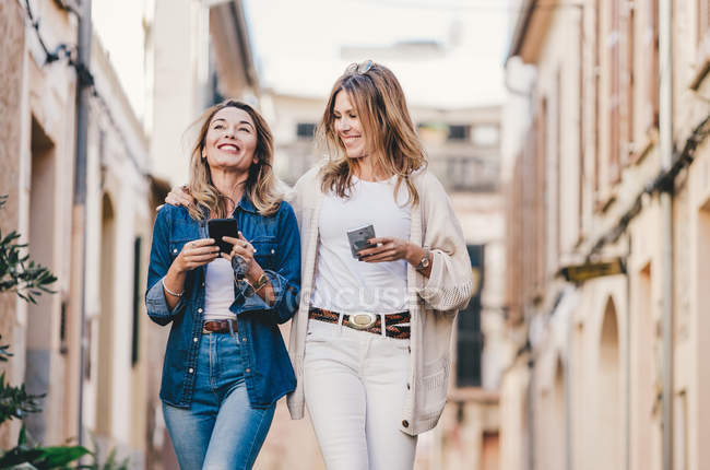 Молоді привабливі усміхнені жінки ходять і спілкуються з мобільними телефонами на вулиці. — стокове фото