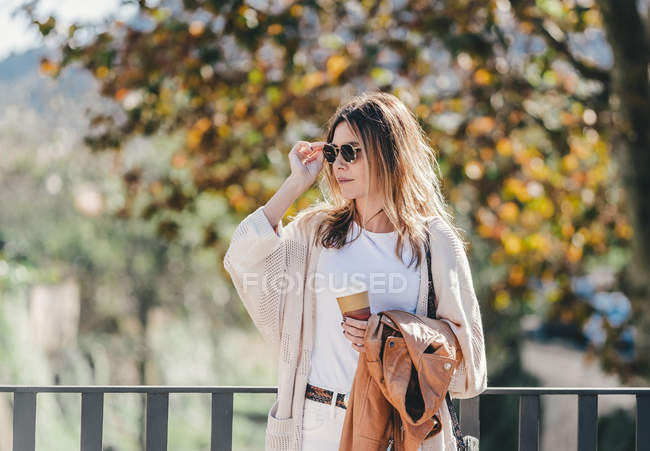 Attractive graceful woman with coffee and jacket in hand looking along leaning on handhold in warm autumn day — Stock Photo