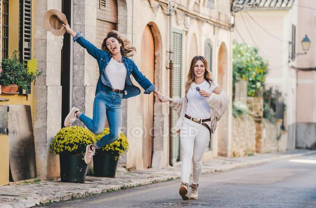 Mulheres sorridentes atraentes pulando e gostando de reunião — Fotografia de Stock