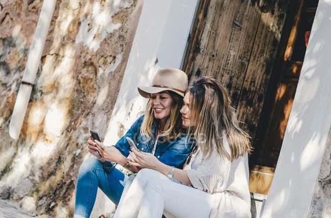 Jeunes femmes souriantes attrayantes assis et messagerie avec des téléphones mobiles dans la rue — Photo de stock