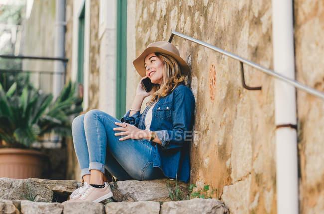 На стіні вимальовується молода усміхнена жінка, яка розмовляє по мобільному телефону і сидить на кам