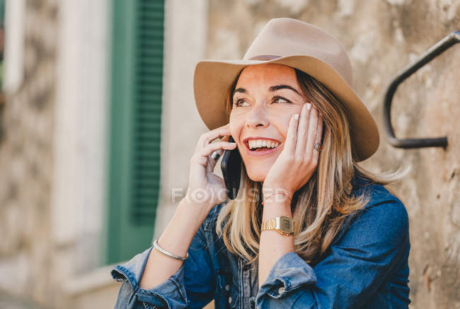 Side view of young smiling woman talking on mobile phone and sitting on stone stairs outside — Stock Photo
